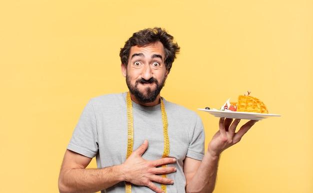 Jovem louco barbudo com uma expressão feliz em dieta e segurando waffles