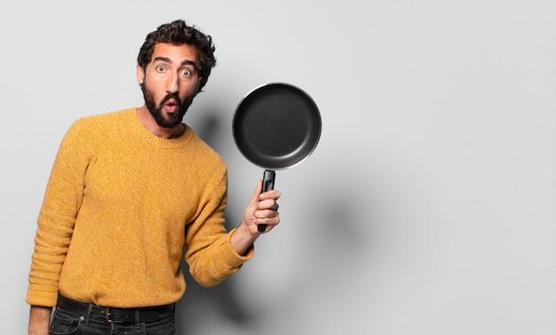 Jovem louco barbudo com uma panela. conceito de cozinhar