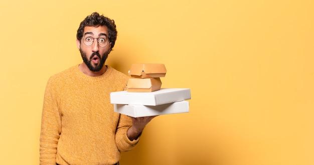 Jovem louco barbudo comendo fast food com um espaço de cópia