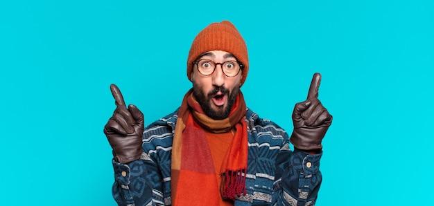 Jovem louco barbudo. expressão de choque ou surpresa e vestindo roupas de inverno