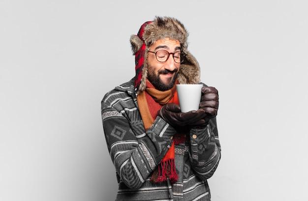 Jovem louco barbudo. expressão feliz e surpresa e vestindo roupas de inverno