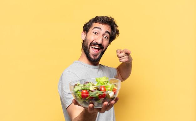 Jovem louco barbudo fazendo dieta apontando ou mostrando e segurando uma salada