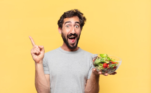 Jovem louco barbudo fazendo dieta comemorando uma vitória bem-sucedida e segurando uma salada