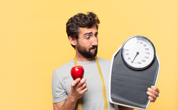 Jovem louco barbudo fazendo dieta duvidosa ou expressão incerta e segurando uma balança e uma maçã