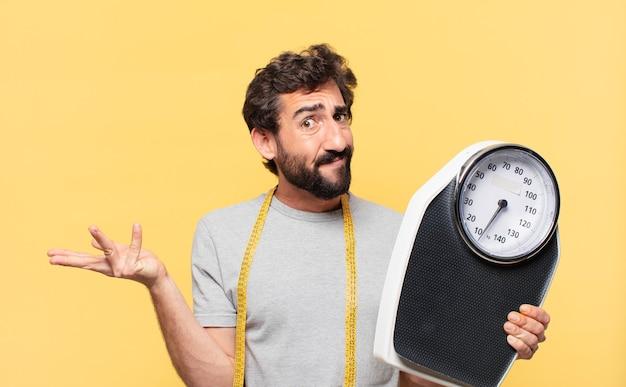 Jovem louco barbudo fazendo dieta duvidosa ou expressão incerta e segurando uma balança leve