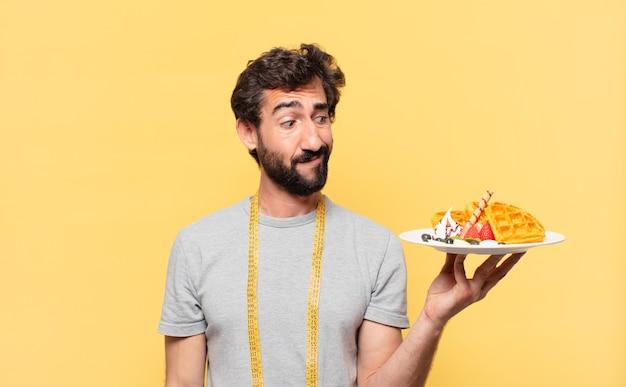 Jovem louco barbudo fazendo dieta duvidosa ou expressão incerta e segurando waffles