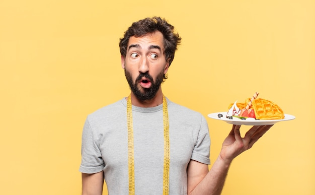 Jovem louco barbudo fazendo dieta e expressão assustada segurando waffles
