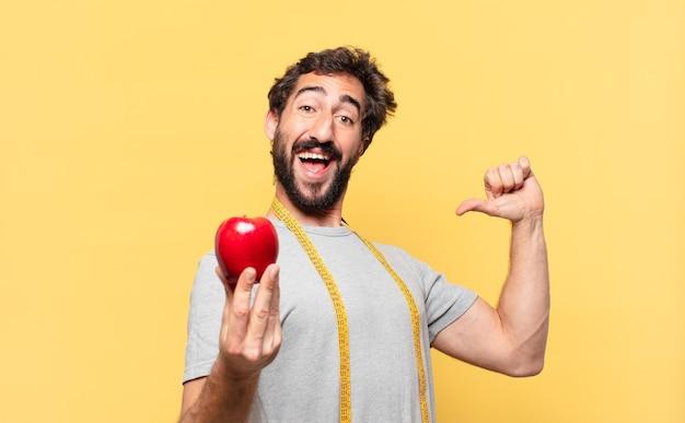 Jovem louco barbudo fazendo dieta e expressão feliz segurando uma maçã