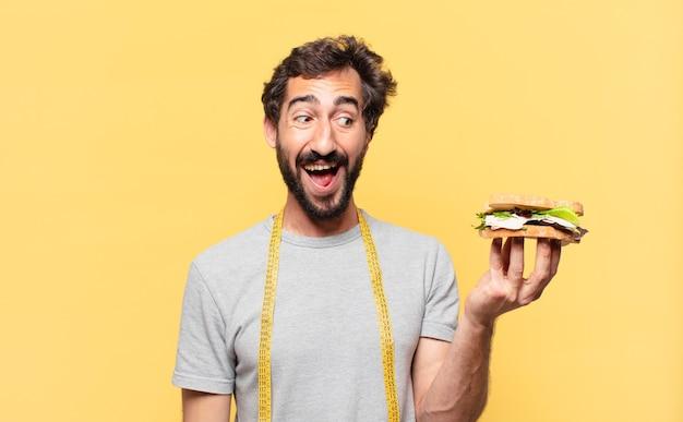 Jovem louco barbudo fazendo dieta expressão de surpresa e segurando um sanduíche
