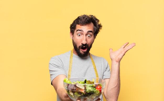 Jovem louco barbudo fazendo dieta expressão de surpresa e segurando uma salada