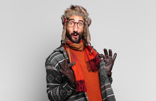 Jovem louco barbudo orgulhoso e feliz e vestindo roupas de inverno