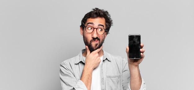 Jovem louco barbudo. pensando ou duvidando da extensão. conceito de tela do telefone