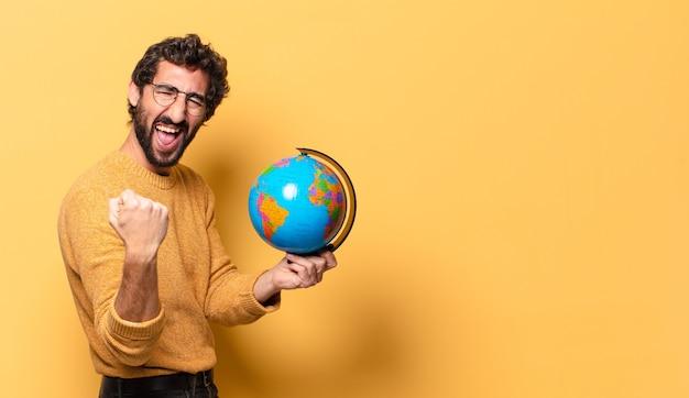 Jovem louco barbudo segurando um mapa do globo do mundo.