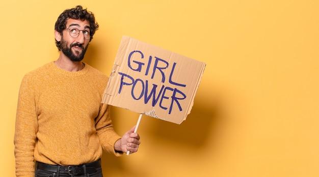 Jovem louco barbudo segurando uma bandeira do poder feminino