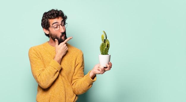Jovem louco barbudo segurando uma planta de cacto