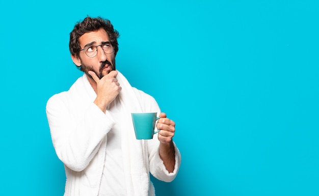 Jovem louco barbudo vestindo roupão de banho e uma xícara de café