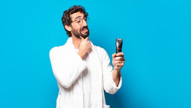 Jovem louco barbudo vestindo roupão de banho fazendo a barba concep