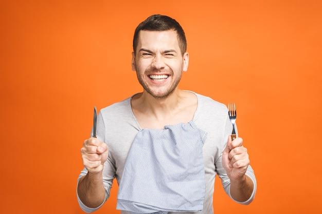 Jovem louco com fome segurando um garfo e uma faca