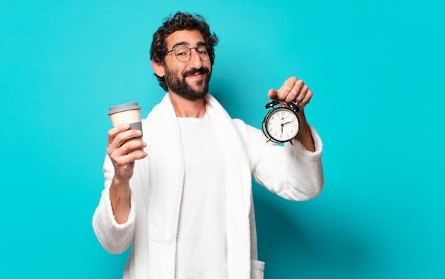 Jovem louco de barba usando roupão de banho e despertador