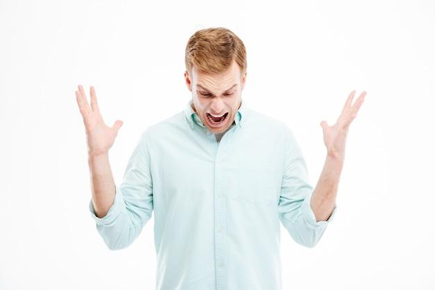 Jovem louco e histérico com as mãos levantadas deixou cair algo, gritando e olhando para baixo