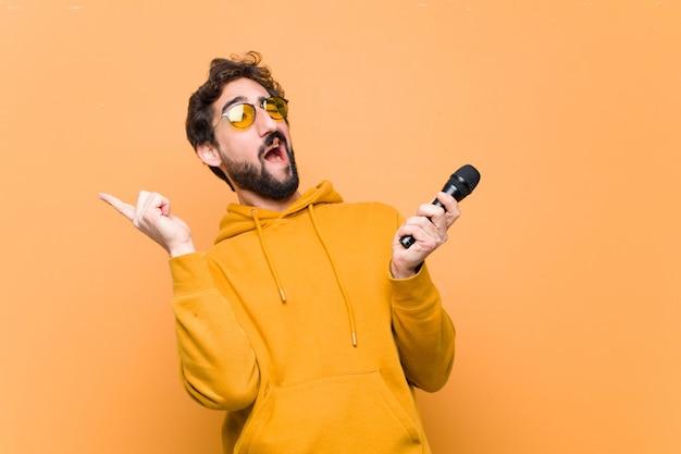 Jovem louco e legal com um microfone na parede laranja
