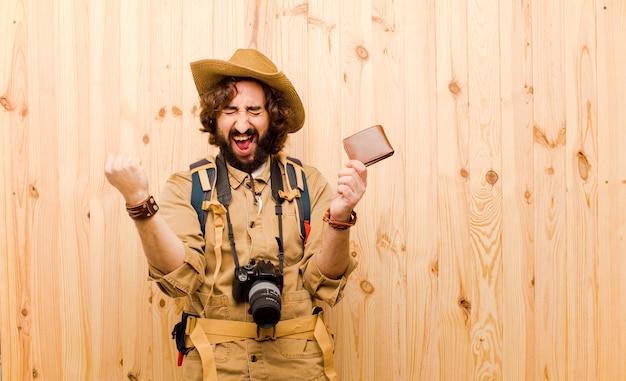 Jovem louco explorador com chapéu de palha e mochila em fundo de madeira