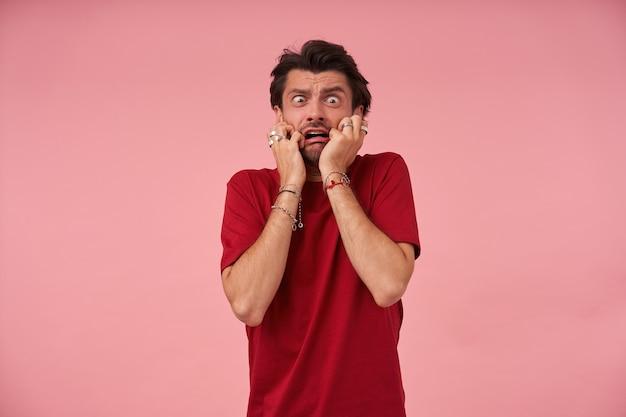 Jovem louco histérico com a barba por fazer na camiseta vermelha fica apavorado e parece em pânico