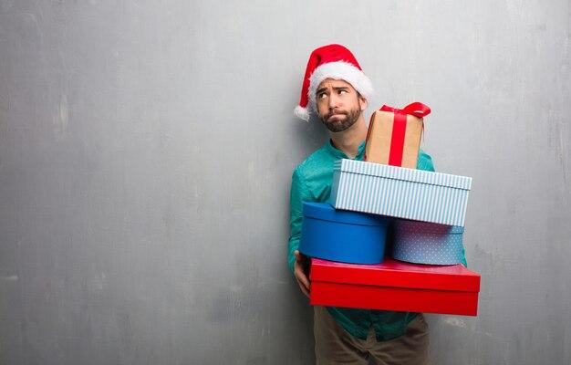 Jovem, louco, homem, segurando, presentes, celebrando, natal