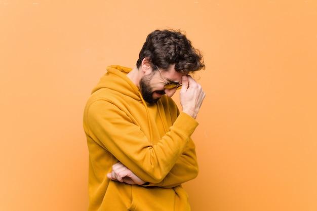 Jovem louco legal com expressão triste contra parede laranja