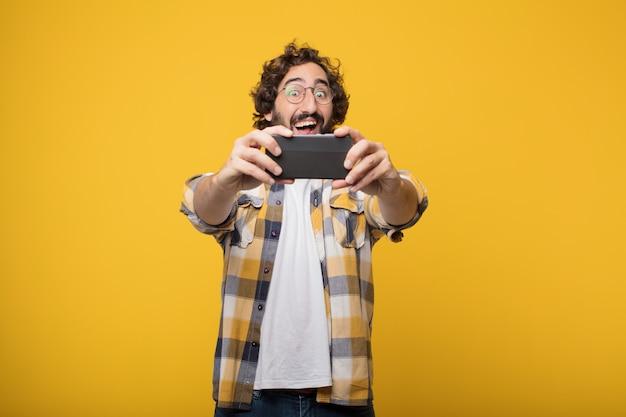 Jovem louco louco idiota posar com um celular inteligente