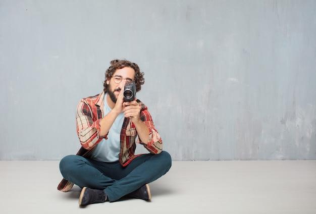 Jovem louco louco idiota posar com uma câmera de cinema vintage