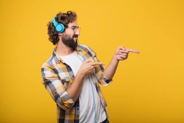 Jovem louco louco idiota posar ouvindo música com um fone de ouvido