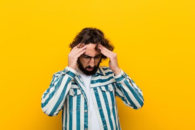 Jovem louco olhando estressado e frustrado, trabalhando sob pressão com dor de cabeça e incomodado com problemas parede amarela