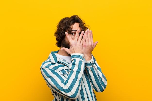 Jovem louco se sentindo assustado, envergonhado, espiando ou espionando com os olhos semicobertos com as mãos parede amarela