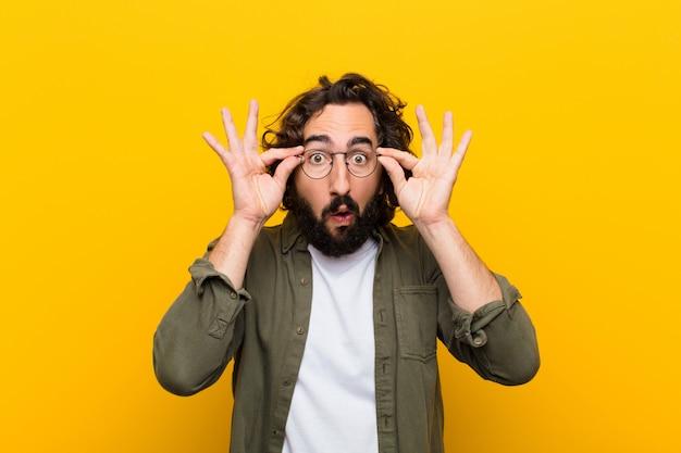 Jovem louco se sentindo chocado, surpreso e surpreso, segurando os óculos com olhar atônito e incrédulo contra a parede amarela