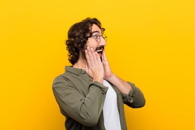 Jovem louco se sentindo feliz, animado e surpreso, olhando para o lado com as duas mãos no rosto contra a parede amarela