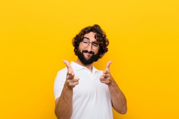 Jovem louco se sentindo feliz, legal, satisfeito, relaxado e bem sucedido, apontando a câmera, escolhendo você parede amarela