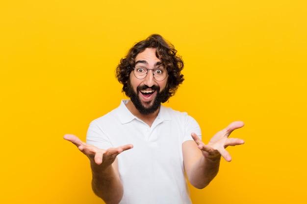 Jovem louco se sentindo feliz, surpreso, sortudo e surpreso, como dizer omg a sério? inacreditável contra parede amarela