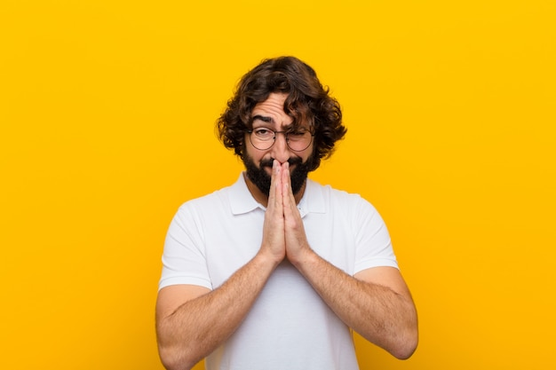 Jovem louco se sentindo preocupado, esperançoso e religioso, orando fielmente com as palmas das mãos pressionadas, pedindo perdão