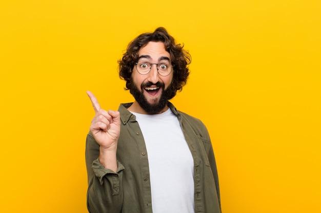 Jovem louco se sentindo um gênio feliz e animado depois de perceber uma idéia, alegremente levantando o dedo, eureka! contra parede amarela