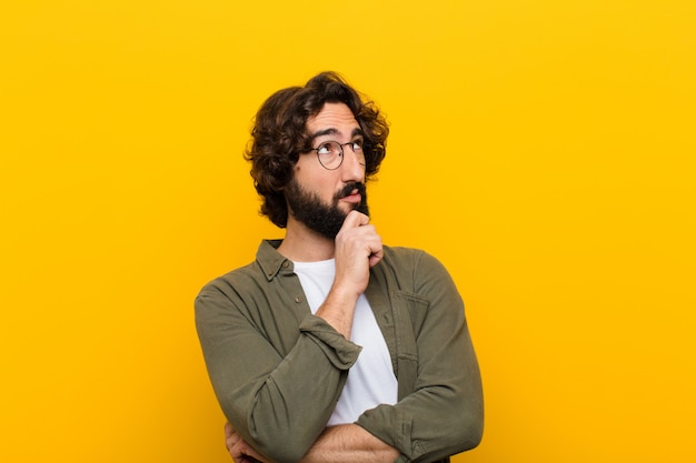 Jovem louco sentindo pensativo, pensando ou imaginando idéias, sonhando acordado e olhando para copyspace contra parede amarela