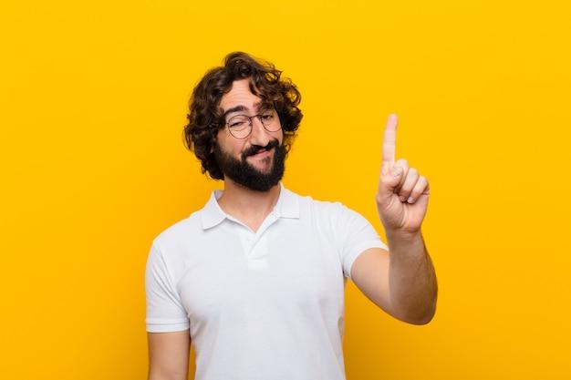 Jovem louco sorrindo e olhando amigável, mostrando o número onefirst com a mão para a frente, contando a parede amarela