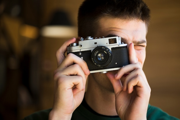 Jovem louco tirando fotos com a câmera vintage