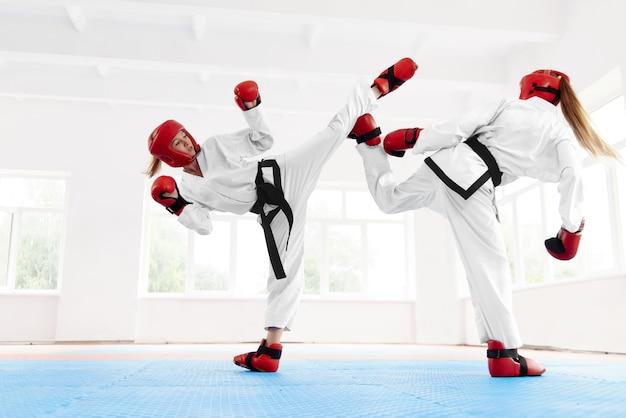 Jovem lutador de boxe feminino, usando a técnica de karatê.