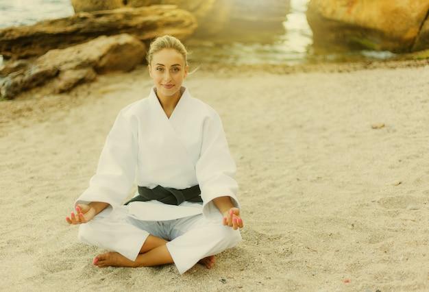 Jovem lutadora atraente em um quimono branco e faixa preta meditando em uma praia selvagem com pedras