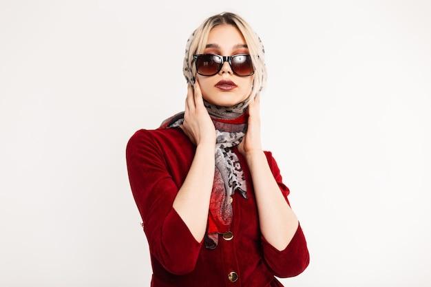 Jovem luxuosa com lenço de leopardo vintage na cabeça com óculos de sol da moda em vestido vermelho elegante posando