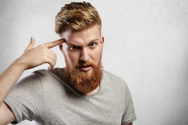 """Jovem machão caucasiano com barba loira e cabelo estilo moderno apontando o dedo para sua têmpora e significando """"use seu cérebro!"""". um cara bonito em uma camiseta cinza casual fica surpreso e ligeiramente irritado."""