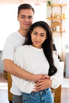 Jovem, macho, abraçando, étnico, namorada, e, olhando câmera