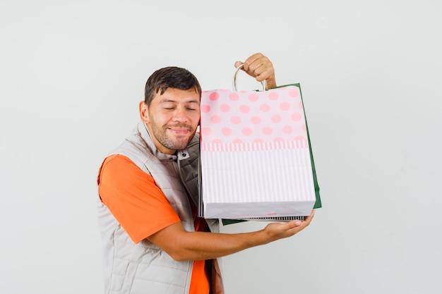 Jovem macho abraçando sacolas de compras em t-shirt, jaqueta e bonito. vista frontal.