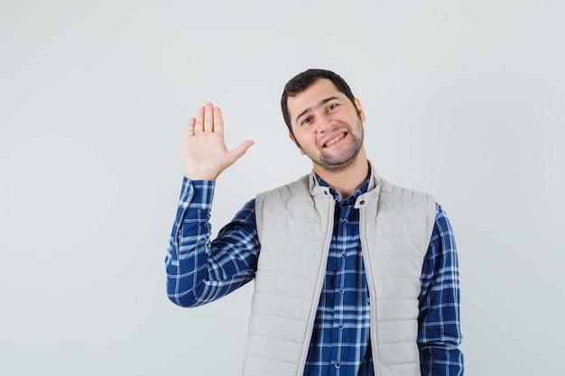 Jovem macho acenando com a mão para saudação na camisa, jaqueta sem mangas e parecendo satisfeito, vista frontal.